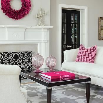 Martha O'Hara Interiors - living rooms - gray walls, gray wall color, pink and gray living room, gray and white rug, gray and white patterned rug, matching sofas, white sofa, pink and white pillow, glossy black coffee table, black lacquered coffee table, pink glass vase, hot pink book, traditional fireplace, ornate fireplace screen, fireplace screen, pink wreath, wreath over fireplace, black french doors, black interior french doors, crystal chandelier, crown molding, pink and gray room, pink wreath, feather wreath, pink feather wreath, black lacquered coffee table, white and gray rug, face to face sofas, revere pewter,
