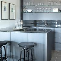 Kelly Deck Design - basements - wet bar, wet bar ideas, steel gray cabinets, wet bar cabinets, speckled counters, speckled countertops, black counters, black countertops, black speckled countertops, glass shelves, wet bar shelves, stacked glass shelves, industrial bar stools, black industrial bar stools, wet bar sink,