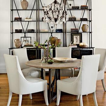 Lindsey Meadows - dining rooms: white walls, white wall color, hardwood floors, gray leather dining chair, gray leather chair, round dining table, round stone topped dining table, iron dining table with stone top, industrial bookcase, stacked books, rustic jar, crystal chandelier, industrial bookshelves, light gray leather dining chair, industrial bookshelf, industrial bookshelf,