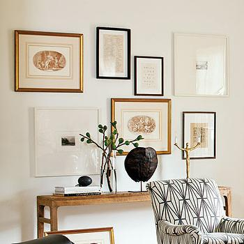Lindsey Meadows - entrances/foyers: white walls, white wall color, slim wooden console table, wooden console table, black framed art print, gold framed art print, white framed art print, gallery wall, gallery wall over console table, stacked books, glass vase, branches, turtle shell, tortoise shell, gold sculpture, black and white armchair, graphic black and white armchair, armchair upholstered in Kelly Wearstler Katana Fabric, Kelly Wearstler Katana Fabric, art over console table,