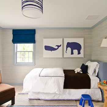 Lauren Stern Design - boy's rooms - blue and gray boys room, gray and blue boys bedroom, gray grasscloth, gray grasscloth wallpaper, silver gray grasscloth, silver gray grasscloth wallpaper, gray crown molding, gray base boards, gray door, indigo blue roman shades, blue roman shades, gray window moldings, whale art, elephant art, kids art, boys art, blue headboard, kids headboard, blue linen headboard, white and brown bedding, hotel bedding, brown blanket, tree stump table, cobalt blue stool, step stool, white and brown rug, white and brown striped rug, brown accent chair, brown tufted chair,