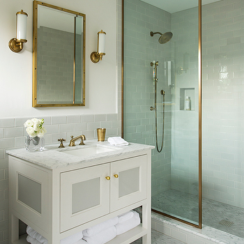 Nina Farmer Interiors - bathrooms - brass trimmed shower enclosure, gray subway tile, gray subway tiled backsplash, gray subway tiled shower surround, marble shower floors, marble tiled shower floor, herringbone marble tile, herringbone marble floor tile, white vanity, gray and white vanity, white vanity with gray paneled doors, brass hardware, white towels, marble counter, marble countertop, brass faucet, brass mint julep cup, glass vase, white flowers, brass mirror, brass vanity mirror, brass sconces, brass and glass sconce, brass and white glass sconce, brass shower head, brass shower kit, star flushmount, brass star shapped flushmount, Visual Comfort Studio Star 1 Light Flush Mount in Hand-Rubbed Antique Brass, brass shower partition, antique brass shower partition, brass mirror, brass sconce, antique brass sconce,