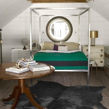Country Living - bedrooms: white wood paneled walls, wood paneled walls, wood paneled ceilings, wood paneling, beams, attic bedroom, loft bedroom, hardwood floors, cowhide rug, gray cowhide rug, round pedestal table, pedestal table, stacked books, round window, round attic window, modern steel canopy bed, canopy bed, steel canopy bed, polished steel canopy bed, white walls sconces, mismatched nightstands, globe, table lamp with gold shade, gold lamp shade, green blanket with navy stripe, white bedding, white bed linens, beige pillow, hardwood floors, distressed hardwood floors, cowhide, gray cowhide, Ikea cowhide rug, metal canopy bed,