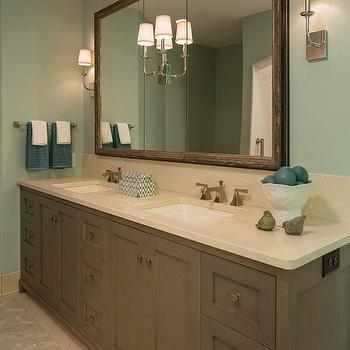 Renae Keller - bathrooms: blue walls, blue wall color, gray vanity, gray bathroom vanity, dual vanity, dual sinks, his and hers sinks, tiled floors, stone tiled floors, gray rug, framed vanity mirror, inset sconce, nickel sconce, nickel double arm sconce, teal hand towels, decorative chevron box, white vase, teal stones, vanity length mirror, framed vanity mirror, vanity length framed mirror, recessed lighting, pot lights, dual vanity, dual vanity ideas, gray double vanity, gray dual vanity, silver marlin,