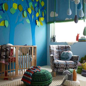 Donna Wilson - nurseries - eclectic nursery, boys nursery, eclectic boys nursery, oval crib, beech crib, paper trees, paper leaves, nursery mural, nursery wall mural, blue walls, nursery with blue walls, nursery roman shade, nursery window treatments, green pouf, olive green rug, patterned chair, blue and brown chair,