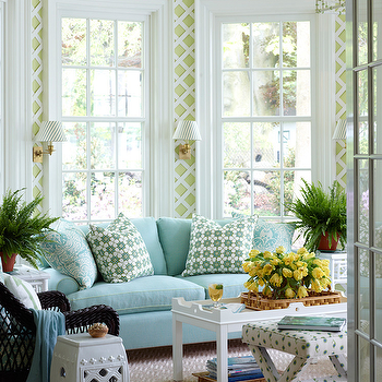 Ashley Whittaker Design - living rooms - sash windows, double hung windows, double hung sash windows, patterned natural fiber rug, natural fiber rug, green and white latticework walls, lattice print walls, latticework walls, green latticework walls, white coffee table, wooden tray, vase of flowers, yellow tulips, aqua blue sofa, blue sofa, blue pillows, green and white patterned pillow, brass wall sconce, sunroom, sun room, white garden stool, black wicker chair, wicker chair, white side table, white end table, ferns, houseplant, green and white x-stool, x-stool, upholstered x-stool, french interior door, glass paned door, aqua sofa, lattice wallpaper,