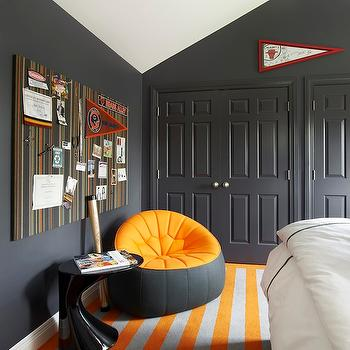 Suzanne Lovell - boy's rooms - vaulted ceiling, charcoal gray wall color, charcoal gray walls, dark gray walls, dark gray wall color, gray walls, gray wall color, gray closet doors, charcoal gray closet doors, pinboard, upholstered pinboard, striped gray white and orange pinboard, gray and orange beanbag, modern black side table, black lacquered side table, striped carpet, wall to wall carpet, gray and orange striped carpet, gray and orange bedroom, gray and orange boys bedroom, striped rug, orange and gray rug, orange and gray striped rug,