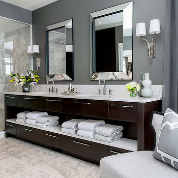 Atmosphere Interior Design - bathrooms - gray walls, gray wall color, marble floor tile, marble tiled floors, marble shower surround, built-in shower bench, shower seat, shower bench, marble tile, contemporary coffee stained vanity, coffee stained open vanity, white towels, white counter, white countertop, polished nickel hardware, gray drapes, gray draperies, gray accent chair, gray and white geometric pillow, mirror framed mirror, dual vanity, his and hers sinks, polished nickel sconce, two arm polished nickel sconce, gooseneck faucet, seamless glass shower, seamless glass shower surround, walk-in shower, flowers, vase of lilies, brown double washstand, dark brown double vanity,