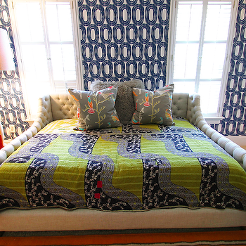 Lucy and Company - boy's rooms - tufted linen bed, tufted bed with tufted sides, tufted linen bed with raised tufted linen sides, beige wall to wall carpet, wall to wall carpeting, wall to wall carpet, beige carpet, blue and green patterned bedding, blue and green bohemian bedding, blue and green boho bedding, gray floral pillow, gray mongolian wool pillow, green glass table lamp, blue dresser, orange nightstand, asian nightstand, orange asian nightstand, stacked books, wallpapered headboard wall, bed in front of window, geometric wallpaper, blue and white geometric wallpaper, wallpaper accent wall, contemporary blue and white wallpaper, white floor lamp, modern white floor lamp, rug on carpet, rug over carpet, orange rug, tall windows, velvet tufted bed,