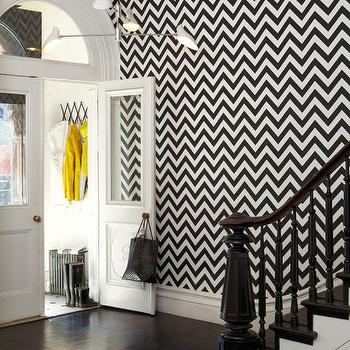 Martyn Lawrence Bullard Design - entrances/foyers - black and white wallpaper, modern black and white wallpaper, black and white chevron wallpaper, chevron wallpaper, zig zag wallpaper, glossy black stairs, black stairs, glossy black newel post, glossy black hand rail, glossy black staircase, glossy black stairway, black staircase, black stairway, dark hardwood floors, hardwood floors, modern white pendant, modern white 4 light pendant, contemporary white 4 light pendant, white four light pendant, double front doors, white glass paned double front doors, white front doors, arched transom window, accordion coat rack, accordion wall mount coat rack, black and white entryway, black and white room, black and white foyer, black and white staircase, black and white stairs, , Fez Noir Wallpaper,