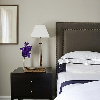 Denai Kulcsar Interiors - bedrooms - white and navy bedding, white and navy sheets, white and navy blue bedding, white and navy blue sheets, dark gray headboard, gray linen headboard, black nightstand, seagrass tray, purple orchid, slim table lamp,