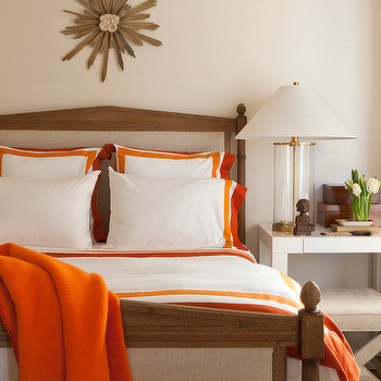 Benjamin Dhong - bedrooms - orange and white bedding, white bedding with orange border, white bed linens with orange border, white duvet with orange border, white pillow shams with orange border, orange throw, wooden sunburst, french style bed, french style linen bed, french style linen upholstered bed, modern white nightstand, white parsons nightstand, white parsons style nightstand, x-bench, white x-bench, brass and glass table lamp, glass table lamp with brass accents, stacked books, vase of flowers, white walls, white wall color, Ralph Lauren Modern Table Lamp in Glass with Brass accents, white and orange duvet, white and orange shams,