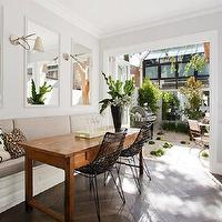 dining rooms - herringbone floor, wood herringbone floor, herringbone wood floor, long dining room, long banquette, long dining banquette, white framed mirrors, desk as dining table, desk used as dining table, metal dining chairs,