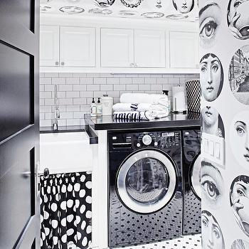 Berkley Vallone - laundry/mud rooms - black and white tiled floor, black and white floor tile, vintage style black and white floor tile, skirted farm sink, skirted farmhouse sink, black and white polka dot skirted sink, white cabinets, white cabinetry, white laundry room cabinets, white laundry room cabinetry, nickel hardware, modern nickel hardware, black and white face wallpaper, modern black and white wallpaper, black and white faces wallpaper, wallpaper in laundry room, graphic black and white wallpaper, black front loading washer, black front loading dryer, front loading washer, front loading dryer, black counters, black countertops, thick black counter, thick black countertop, subway tile, white subway tile, subway tiled backsplash, black door, black interior door, folding counter, modern spray faucet, farm sink, farmhouse sink, apron sink, gray grout, laundry room, black and white laundry room, black and white laundry room, small farmhouse sink, mini farmhouse sink, white subway tile with black grout, skirted sink, skirted laundry sink, skirted laundry room sink, laundry room wallpaper, wallpaper in laundry room, Fornasetti Wallpaper,