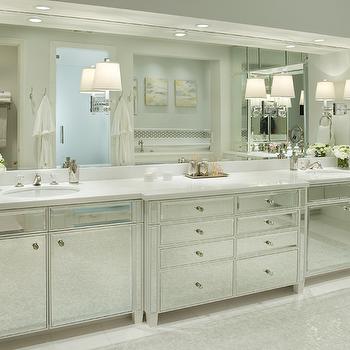 Berkley Vallone - bathrooms - mirrored vanity, mirrored bathroom vanity, mirrored sink vanity, mirrored dual sink vanity, crystal hardware, white counter, white countertop undermount sink, dual sinks, his and hers sink, frameless vanity mirror, inset sconces, sconces inset to vanity mirror, vanity mirror with inset sconces, polished nickel sconces, marble floor tile, pearlescent mosaic tiled floors, crystal hardware, recessed lighting, pot lights, gray walls, gray wall color, mirror fronted sink vanity, mirror fronted bathroom vanity, towel ring, white towels, white hand towels, vase of flowers, white flowers, pearlescent mosaic tile, mirrored washstands, mirrored bath vanity, mirrored bathroom vanity, mirrored sink vanity,