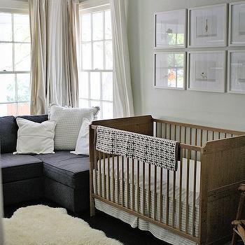Project Nursery - nurseries - sheepskin rug, hardwood floors, dark hardwood floors, white pillow, sash windows, double hung windows, double hung sash windows, white drapes, white curtains, drum pendant, pierced white drum pendant, gray walls, gray wall color, gender neutral nursery, wood crib, wooden crib, white crib bedding, beige and white striped crib bedding, brown and white geometric throw, geometric throw, framed animal photos, framed baby animal photos, framed baby animal photography, baby animal art, Sharon Montrose The Animal Print Shop, sofa in nursery, nursery sofa, guest room and nursery, art over crib, art above crib, The Animal Print Shop,