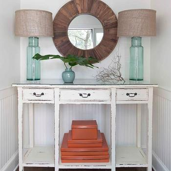 Erin Glennon Interiors - entrances/foyers - white walls, white wall color, beadboard, beadboard half wall, beadboard paneling, beadboard paneled walls, white beadboard, beadboard wainscoting, hardwood floors, orange boxes, distressed white console, distressed white console table with drawers, blue glass table lamp, aqua glass table lamp, beachy entryway, beachy foyer, nautical entryway, nautical foyer, branches, ginger jar, palm fronds, round salvaged wood mirror, round distressed wood mirror, round mirror, blue glass lamp with burlap shade, aqua glass lamp with burlap shade, beadboard half wall, distressed console table, cottage foyer, recycled glass lamps, orange stacking boxes,