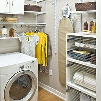 Organized Living - laundry/mud rooms - yellow and gray laundry room, laundry room, light gray walls, laundry room shelves, laundry room cabinets, laundry room bins, cabinet with pull out bins, wall mounted ironing board, ironing board, ironing board on wall, wall ironing board, laundry room cabinets,