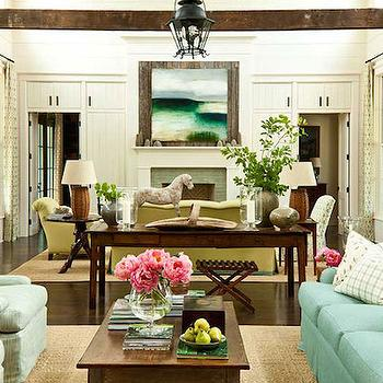 Southern Living - living rooms - long living room, 2 sitting areas, turquoise sofa, turquoise blue sofa, ivory and turquoise pillows, wood coffee table, seafoam green chairs, bound sisal rug, console table, paneled walls, white wall paneling, white paneled walls, rustic wood beams, herringbone doors,