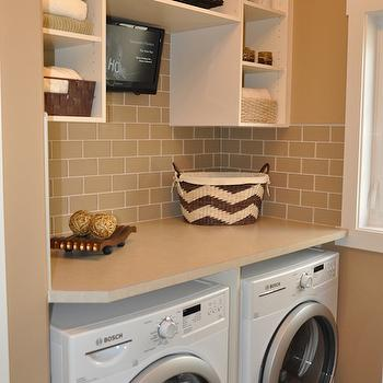 Sarasota Homes - laundry/mud rooms: chevron basket, upper cabinets, laundry room cabinets, open cabinets, beige subway tiles, white washer and dryer, front load washer and dryer,