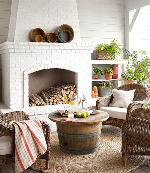 Country Living - decks/patios - siding, wood siding, outdoor fireplace, white brick fireplace, white brick outdoor fireplace, herringbone firebox, round jute rug, round braided jute rug, re-purposed wine barrel coffee table, reclaimed wine barrel coffee table, wicker chair, white shelves, outdoor shelving, potted plants, outdoor living room, outdoor living area, outdoor seating, striped red and white throw, covered patio with fireplace, patio fireplace, outdoor fireplace, barrel table, barrel coffee table, wine barrel table, wine barrel coffee table, wicker armchairs, round rug, seagrass rug, round seagrass rug,