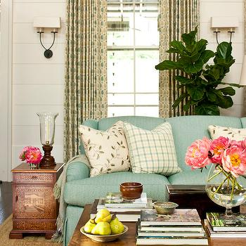 Southern Living - living rooms - paneled walls, white wall panels, white wall paneling, wall paneling, twist sconces, bronze twist sconce, yellow and blue curtains, yellow and turquoise curtains, yellow and turquoise drapes, turquoise sofa, turquoise couch, turquoise linen sofa, turquoise linen couch, turquoise blue sofa, turquoise blue couch, fiddle leaf fig, wood coffee table, rustic wood coffee table, bound sisal rug, ivory and turquoise pillows,
