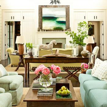 Southern Living - living rooms - long living room, 2 sitting areas, turquoise sofa, turquoise blue sofa, ivory and turquoise pillows, wood coffee table, seafoam green chairs, bound sisal rug, console table, paneled walls, white wall paneling, white paneled walls, rustic wood beams, herringbone doors, multiple sitting areas, yellow sofa, yellow chairs, faux bois end tables, round faux bois tables, seagrass lamps, seagrass table lamps, fireplace, living room fireplace, square mirror, fireplace mirror, square mirror, salvaged wood mirror,