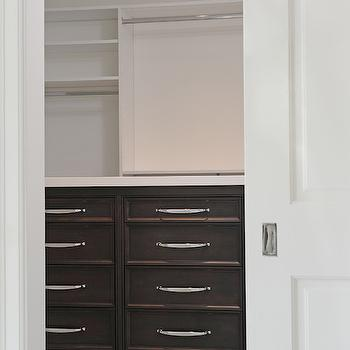 Kelly Baron - closets - pocket door, white pocket door, white walls, white wall color, recessed lighting, pot lights, closet, walk-in closet, walk-in wardrobe, closet system, closet built-ins, dresser drawers, closet dresser drawers, black-brown stained cabinets, black-brown stained dresser drawers, clothes rails, closet shelving, closet shelves, closet pocket door, nickel hardware, pocket door, closet pocket door, closet with pocket door,
