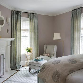 Liz Caan Interiors - bedrooms: elegant bedroom, corner fireplace, bedroom fireplace, quatrefoil mirror, mirror over fireplace, white quatrefoil mirror, herringbone tiles, marble herringbone tiles, white marble herringbone tiles, fireplace surround, herringbone fireplace surround, marble herringbone fireplace surround, sage green curtains, sage green drapes, patterned curtains, patterned drapes, lavender walls, medallion bedding, medallion duvet, reading corner, bedroom reading corner, round directoire table, brass directoire table, white marble top directoire table, brass floor lamp, swing arm floor, lamp, brass swing arm floor lamp, gray wingback chair, gray ottoman, lattice rug, gray lattice rug,