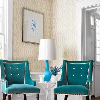 Thibaut Design - living rooms - beige and ivory geometric wallpaper, geometric wallpaper, beige and ivory trellis wallpaper, beige and ivory lattice wallpaper, lattice wallpaper, trellis wallpaper, wainscoting, white faux bois side table, hardwood floors, teal velvet chair, contemporary teal velvet chair, teal velvet chair with white button tufting, teal chair, blue table lamp, modern blue table lamp, contemporary blue table lamp, white branch side table, vase of flowers, crown molding, window molding, teal chairs,
