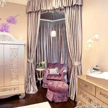 Little Crown Interiors - nurseries - greige walls, greige wall color, hardwood floors, dark hardwood floors, silver armoire, silver nursery armoire, silk drapes, silk curtains, curtained nook, lavender silk drapes, lavender silk curtains, purple velvet armchair, purple velvet tufted ottoman, silver changing table, purple wall art, purple nursery art, white wall sconce, purple nursery, lavender nursery, wall mural, orchid wall mural, purple orchid wall mural, white crystal droplet wall sconce, white wall sconce, crystal droplet wall sconce, purple and gray nursery, lavender valance, silver armoire, nursery armoire, nursery nook, nursery alcove, girls nursery, crushed velvet chair, crushed velvet ottoman, purple velvet glider, purple crushed velvet glider, purple crushed velvet ottoman, purple velvet ottoman, round purple ottoman,