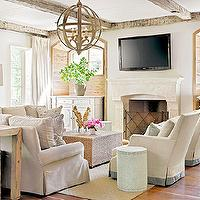 Elegant living room with flat screen TV over carved stone fireplace with iron ...