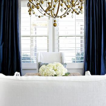 Shea McGee Design - dining rooms - Benjamin Moore - Balboa Mist - navy dining room, navy blue dining room, white and navy dining room, white and navy blue dining room, navy curtains, navy blue curtains, navy drapes, navy blue drapes, greek key trim, navy greek key trim, gold chandelier, beaded chandelier, gold beaded chandelier, restoration hardware dining table, extension dining table, salvaged wood dining table, restoration hardware dining chairs, slipcovered dining chairs, slipcovered wingback dining chairs, linen slipcovered dining chairs, navy silk curtains, navy blue silk curtains, brass drapery rods, dining room chandelier, navy blue silk drapes,