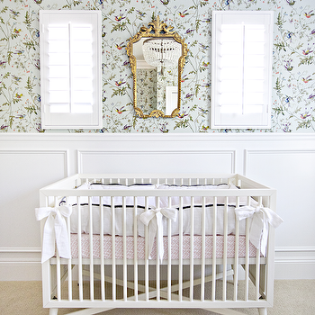 Shea McGee Design - nurseries - wainscoting, nursery wainscoting, wainscoting in nursery, nursery wallpaper, birds wallpaper, aviary wallpaper, wallpaper for nursery, ornate mirror, gold ornate mirror, mirror over crib, mirror above crib, white crib, nursery crib, girls crib bedding, girl nursery, DwellStudio Mid-Century French White Crib, Vanuatu Twilight Wallpaper,