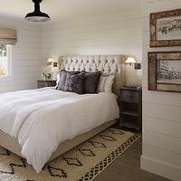 Monochromatic bedroom with shiplap paneled walls over gray washed hardwood floors ...