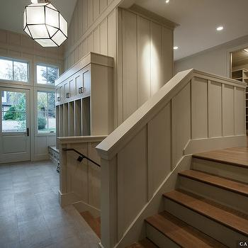 Cameo Homes - laundry/mud rooms - gray board and batten, board and batten, wood paneled walls, wood paneling, gray walls, gray wall color, paneled walls, glass paned door, glass paned front door, window next to front door, transom window, transom window over front door, frosted glass geometric pendant, zinc and frosted glass pendant, frosted glass pendant lantern, storage lockers, mud room storage, mud room cabinets, mud room lockers, coat hooks, storage bench, mud room built-ins, antique zinc chandelier, antique zinc pendant, faceted chandelier, faceted pendant, gray mudroom lockers, Morris Medium Lantern,