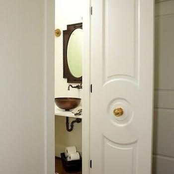 Twin Companies - bathrooms - powder room, powder room door, paneled door, circular paneled door, small powder room, floating vanity, copper sink, bowl sink, copper sink, copper vessel sink, vessel sink, black mirror, metal mirror, white and brown rug, stripe rug, brass doorknob, antique brass doorknob,