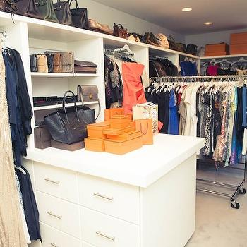 The Coveteur - closets - walk-in closet, walk-in wardrobe, custom closet, closet island, built-in dresser drawers, nickel hardware, clothes rails, clothes rack, movable clothes rail, movable clothes rack, nickel hardware, gray walls, gray wall color, wall to wall carpeting, beige carpet, beige carpeting, gray roman shade, recessed lighting, pot lights, closet organization, organized closet, custom closet design, rolling clothes rack, closet clothes rack, closet island,