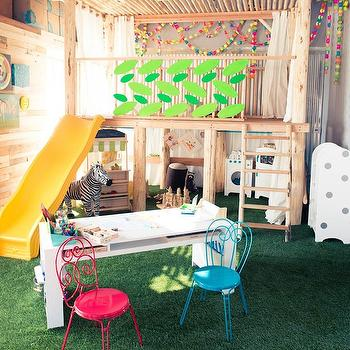 The Coveteur - girl's rooms - playroom, playroom ideas, indoor treehouse, treehouse, treehouse slide, playroom slide, play kitchen, arts and crafts table, play table, play chairs, play table and chairs, faux grass,