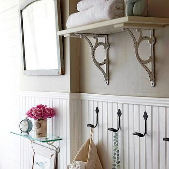 BHG - bathrooms - beadboard, bathroom beadboard, white beadboard, beadboard paneling, white beadboard paneling, cafe au lait walls, cafe au lait wall color, cottage bathroom, beadboard wainscoting, glass shelf, glass bathroom shelf, flowers, gray mirror, rustic mirror, shelf with iron brackets, shelf with iron corbels, beadboard backsplash, cottage bathrooms,