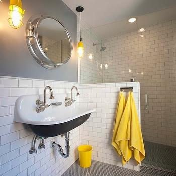 Eric Aust Architect - bathrooms - yellow accents, yellow bathroom accents, yellow and gray bath, yellow and gray bathroom, gray walls, subway tiled walls, subway tile backsplash, half tiled wall, 1/2 tiled wall, bathroom subway tiles, porthole mirrors, marine pendants, brockway sink, shared sink, sink with 2faucets, black penny tiles, black penny floor, walk in shower, subway tile shower, yellow waste basket, yellow pendants, yellow light pendants, Kohler Brockway Sink,