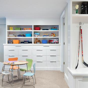 Clean Design Partners - basements - basement, basement playroom, playroom, kids playroom, carpet tiles, beige carpet tiles, built in cabinets, built in bookcases, built in bookcase with drawers, bookcase drawers, built ins, basement built ins playroom built-ins, round play table, chrome based play table, kids table, kids play table, green kids chair, blue kids chair, gray kids chair, orange kids chair, basement mudroom, plat tables and chairs,