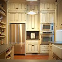 Gorgeous pantry with ivory beadboard cabinets accented with oil-rubbed bronze ...