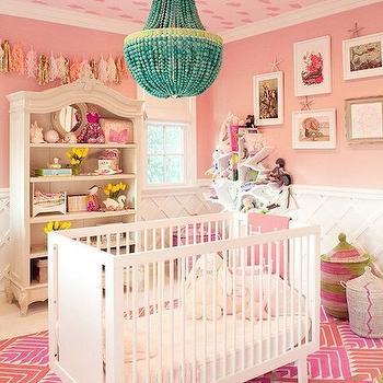 Domaine Home - nurseries: pink nursery, pink walls, pink wall color, white crib, modern white crib, contemporary white crib, pink geometric rug, pink and red geometric rug, african basket, woven african basket, wainscoting, trellis wainscoting, criss cross wainscoting, lattice wainscoting, nursery wainscoting, bookcase armoire, armoire style bookcase, beaded chandelier, turquoise beaded chandelier, gallery wall, nursery gallery wall, white tree bookcase, tree bookcase, tassel banner, pink tassel banner, tasseled banner, modern pink and white rug, cloud patterned ceiling, pink cloud patterned ceiling, white tree bookcase, nursery bookcase, nursery bookshelf, nursery chandelier, pink geometric rug, lattice walls, pink nursery, white and pink nursery, kourtney kardashian, kourtney kardashian nursery, turquoise blue chandelier, chandelier over crib, crib chandelier, nursery crib chandelier,