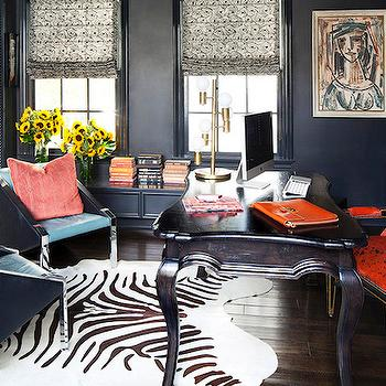 Domaine Home - dens/libraries/offices - navy home office, navy walls, navy wall color, navy bookcase, navy bookshelf, navy built ins, navy built in bookcases, built ins, built in bookcase, built in bookshelf, hardwood floors, dark hardwood floors, zebra print rug, faux zebra hide rug, black desk, black cabriole leg desk, traditional black desk, black and red patterned chair, black and red pattern desk, modern black chair, coral pillow, stacked books, roman shade, vase of flowers, framed art, framed portrait, books organized by color, books stacked by color, color blocked books, color block stacked books, books sorted by color, celebrity home office, patterned roman shade, navy built in bookcase, books arranged by color, navy blue office, navy blue cabinets, cabriole desk, navy moldings, navy window moldings, navy blue moldings, navy blue window moldings, navy blue built ins,