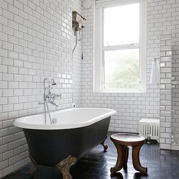 One Fine Stay - bathrooms: white subway tile, subway tile, ceiling height subway tile, ceiling height subway tiled walls, subway tiled walls, dark grout, black grout, gray grout, black floors, black bathroom floor, claw foot tub, black and gold claw foot tub, wooden accent stool, three legged wooden stool, copper pendant, copper pendant shade, modern copper pendant, black claw foot tub with gold feet, black floor, black plank floor, black clawfoot tub, black clawfoot bathtub, bathroom subway tiles,