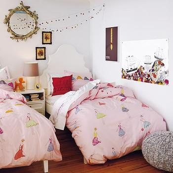 Land of Nod - girl's rooms - white walls, white wall color, gray knit pouf, woven gray pouf, hardwood floors, light hardwood floors, twin beds, twin girls room, white bed, white arched headboard, white arched wooden headboard, girls bedding, pink girls bedding, pink dancer bedding, red pillow, white nightstand, white two drawer nightstand, white table lamp, white table lamp with taupe shade, pom pom garland, faux bois round mirror, gold faux bois mirror, gold faux bois round mirror, kids art, kids wall art, kids wall decor, garland, kids headboards, kids bedding, shared nightstand, shared kids room, shared girls room, girls bedding, pink bedding, pink duvet, Little Twigs Wall Mirror, Monarch Headboard, Monarch Nightstand, Tulle and The Gang Bedding,