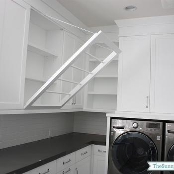 Sunny Side Up - laundry/mud rooms - laundry room, white and grey laundry room, shaker cabinets, white shaker cabinets, laundry room cabinets, subway tiles, laundry room subway tiles, dark gray quartz, dark gray quartz counters, dark gray quartz countertops, silver washer dryer, gray washer dryer, drying racks, clothes drying racks, built in drying racks, pull down drying racks,