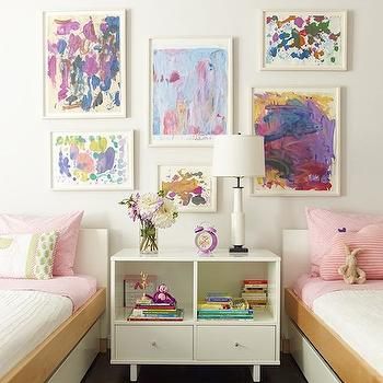 Sawyer Berson - girl's rooms: kids gallery wall, kids room gallery wall, framed kids art, framed kids artwork, gallery wall, girls room gallery wall, hardwood floors, dark hardwood floors, modern white nightstand, extra wide white nightstand, modern white two drawer nightstand, stacked books, purple alarm clock, vase of flowers, white table lamp, vintage white lamp, pink bedding, pink sheets, white bedding, white sheets, twin beds, twin bedroom, white bed, white twin bed, modern white twin bed, white twin bed with wood rail, wide nightstand, shared nightstand, kids nightstand, kids shared nightstand, shared girls room, kids beds,