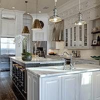 Open concept kitchen with pale gray inset cabinets adorned with nickel hardware ...